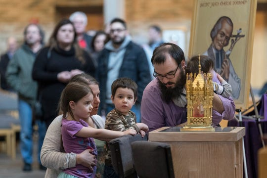 Emily Allasio and her husband John Allasio with their children Sophie, 4, Johnny, 2, and Michael, 11 months, all of Farmington Hills pray by the reliquary which contains physical heart of France's St. John Vianney during Heart of a Priest tour at St. John Vianney Parish in Shelby Township, Saturday, March 30, 2019.
