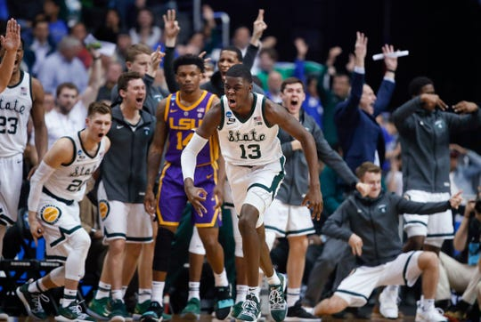 Michigan State forward Gabe Brown (13) and teammates react after he scored against LSU guard Marlon Taylor (14) during the second half.