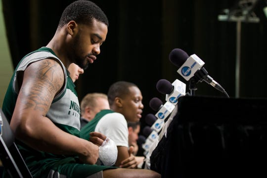Michigan State forward Nick Ward adjusts an ice pack on his hand.