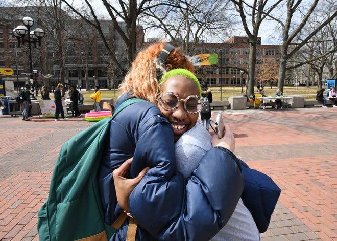 "Friends Sandra Yacoub and Khadija Williams, right, greet each other with a hug on ""The Diag"" on  campus in Ann Arbor.  Williams will graduate this spring, one of the African American students who make up just 4%  of the enrollment at the University of Michigan."