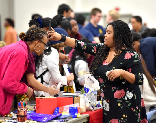 Kaleia Maxey, left, 15, of Chicago, smells essential-oil-scented rice held by WSU psychology and pre-medicine major Gabrielle Gordon, right, of Southfield, before Maxey makes a heating and cooling pack.