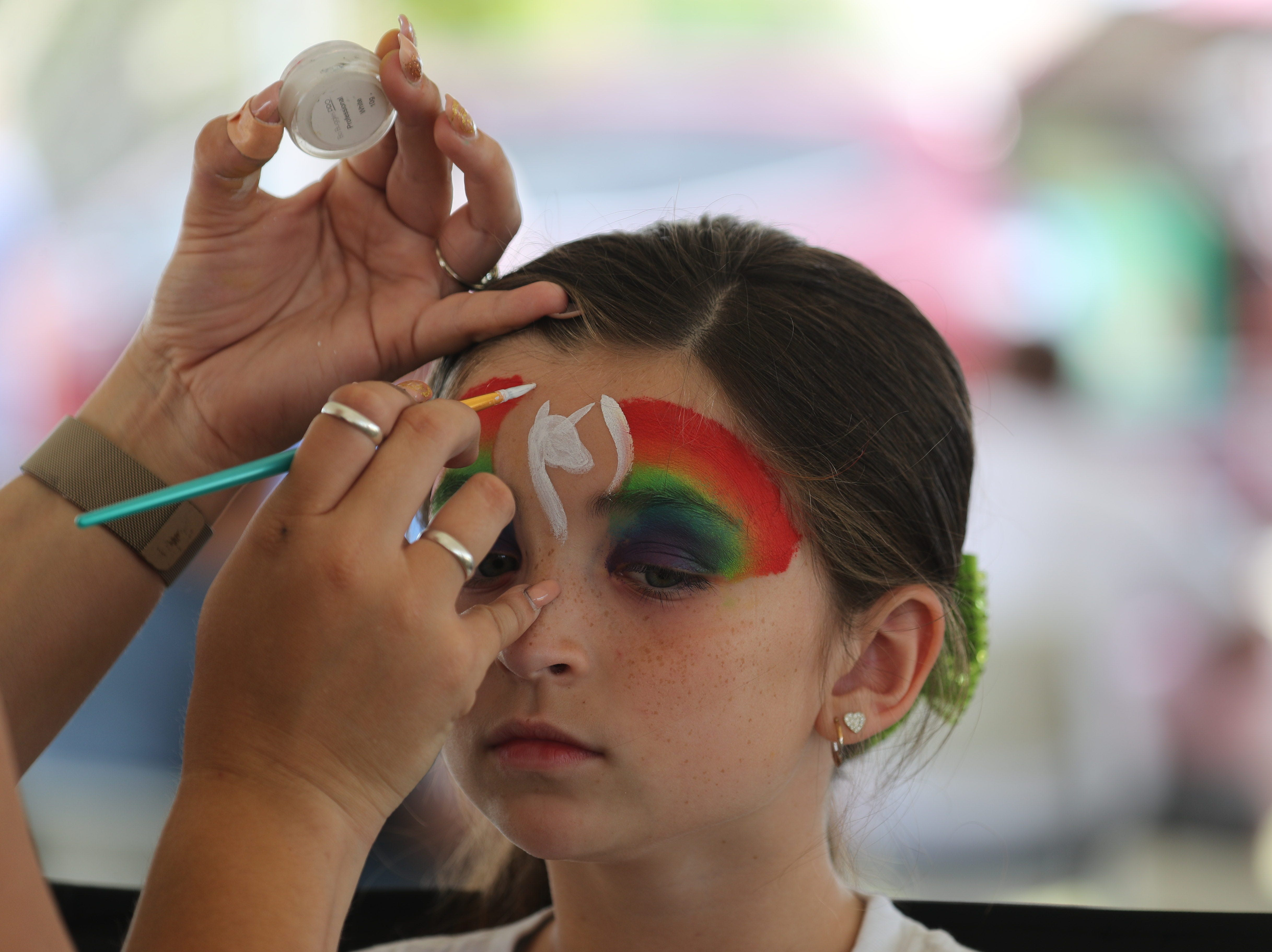 Bella Spinner, 8, has her face painted at the Lights for Layla on Saturday at Cape Assembly in Cape Coral.