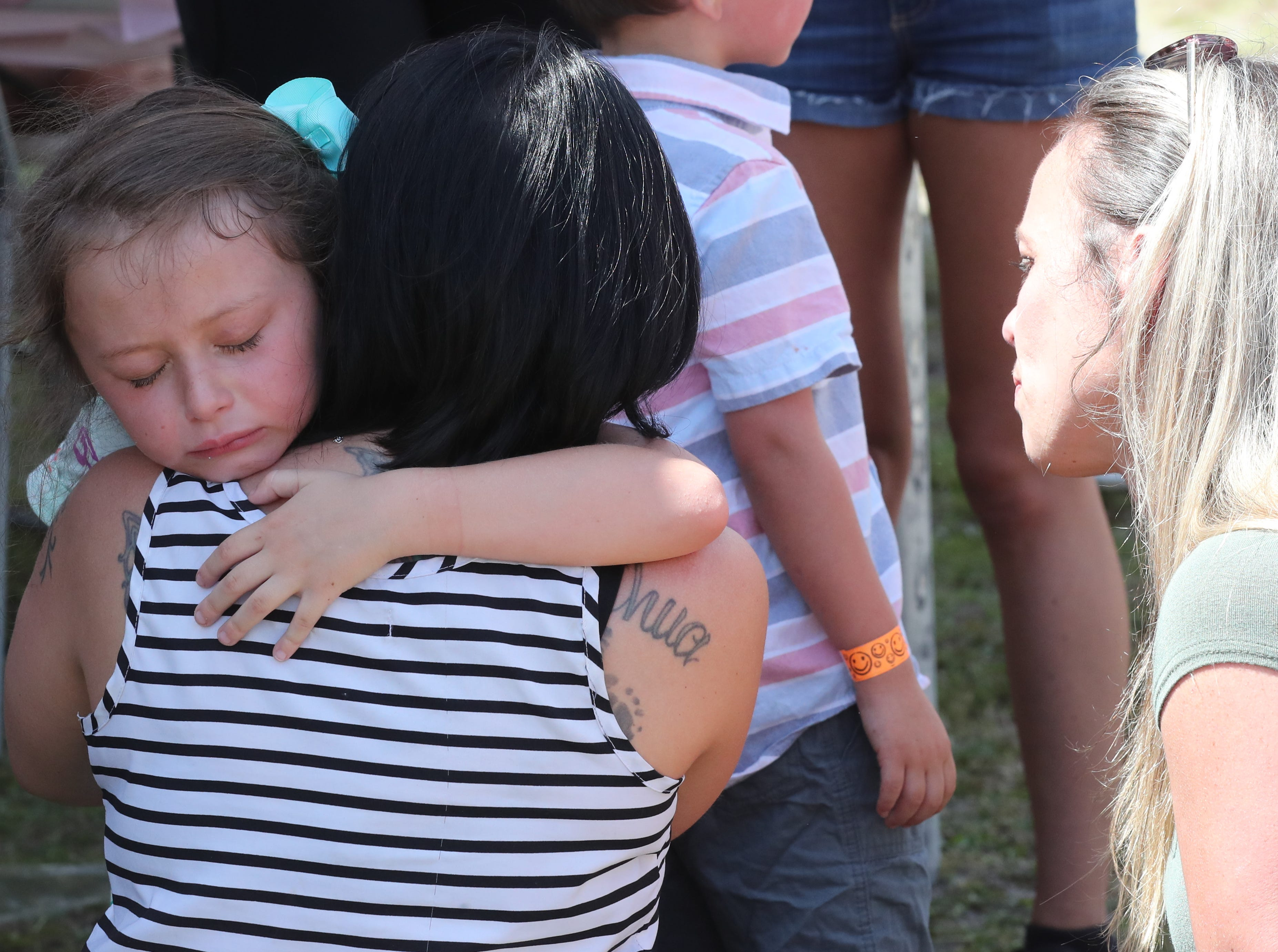 Cheyanne Begle, 7 of Cape Coral and classmate of Layla, hugs Kathleen Aiken, Layla's mom at the event Saturday. Lights for Layla fundraiser. Cheyanne's mom, Samantha Belge looks on.  Lee County students who wait for school buses in the dark morning hours will be able to adorn their backpacks with flashing LED lights starting next year. Local agencies are partnering to raise money for the new safety protocols after the death of 8-year-old Layla Aiken, who was hit by a pickup truck while waiting at her bus stop with her brothers. Layla's family and friends hosted their own fundraiser called Lights for Layla Saturday from 1-3 p.m. at the Cape Assembly church, Cape Coral.
