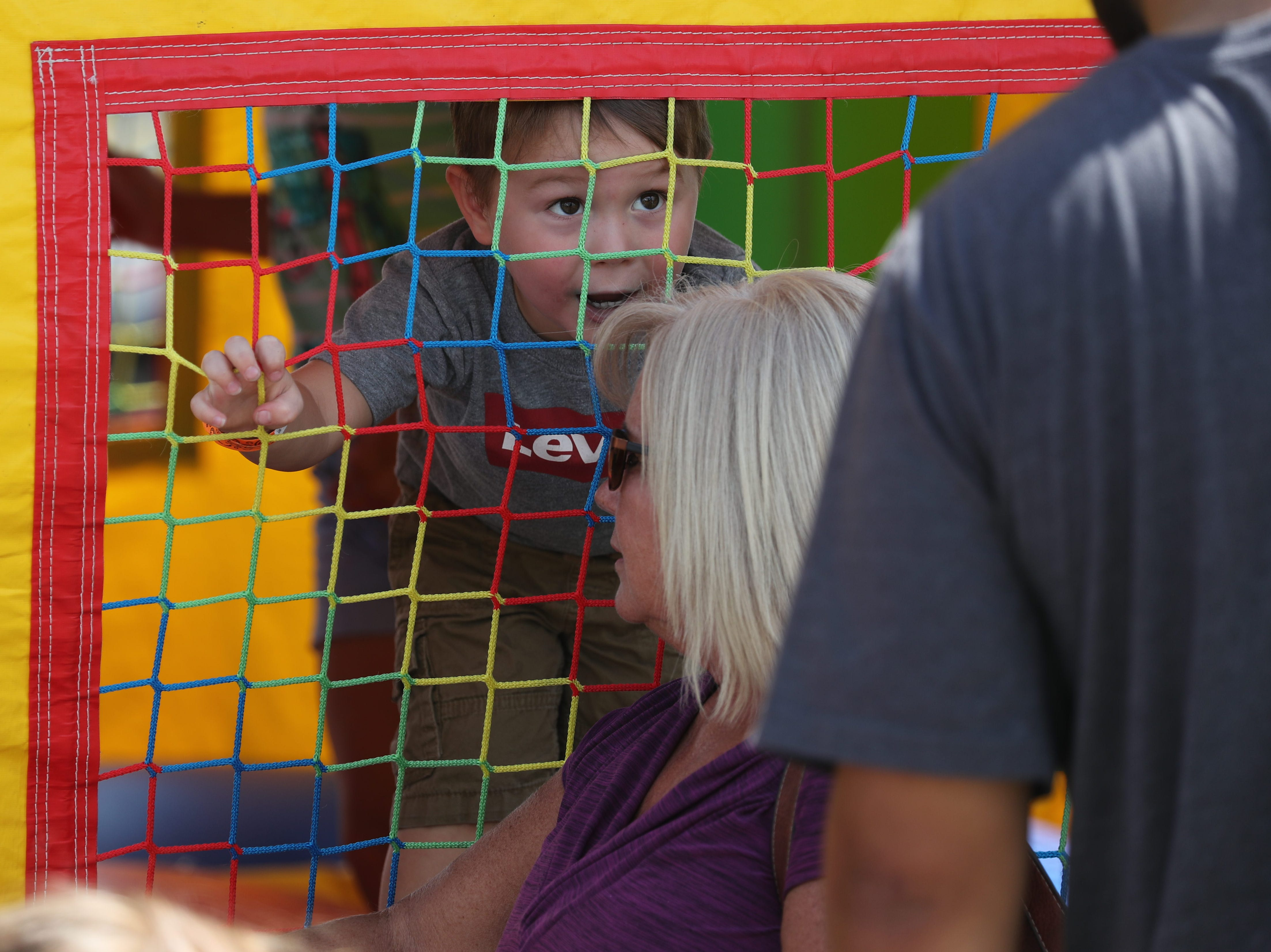Conner Zamorano, 3, looks out from the bounce house at the Lights for Layla fundraiser Saturday in Cape Coral.