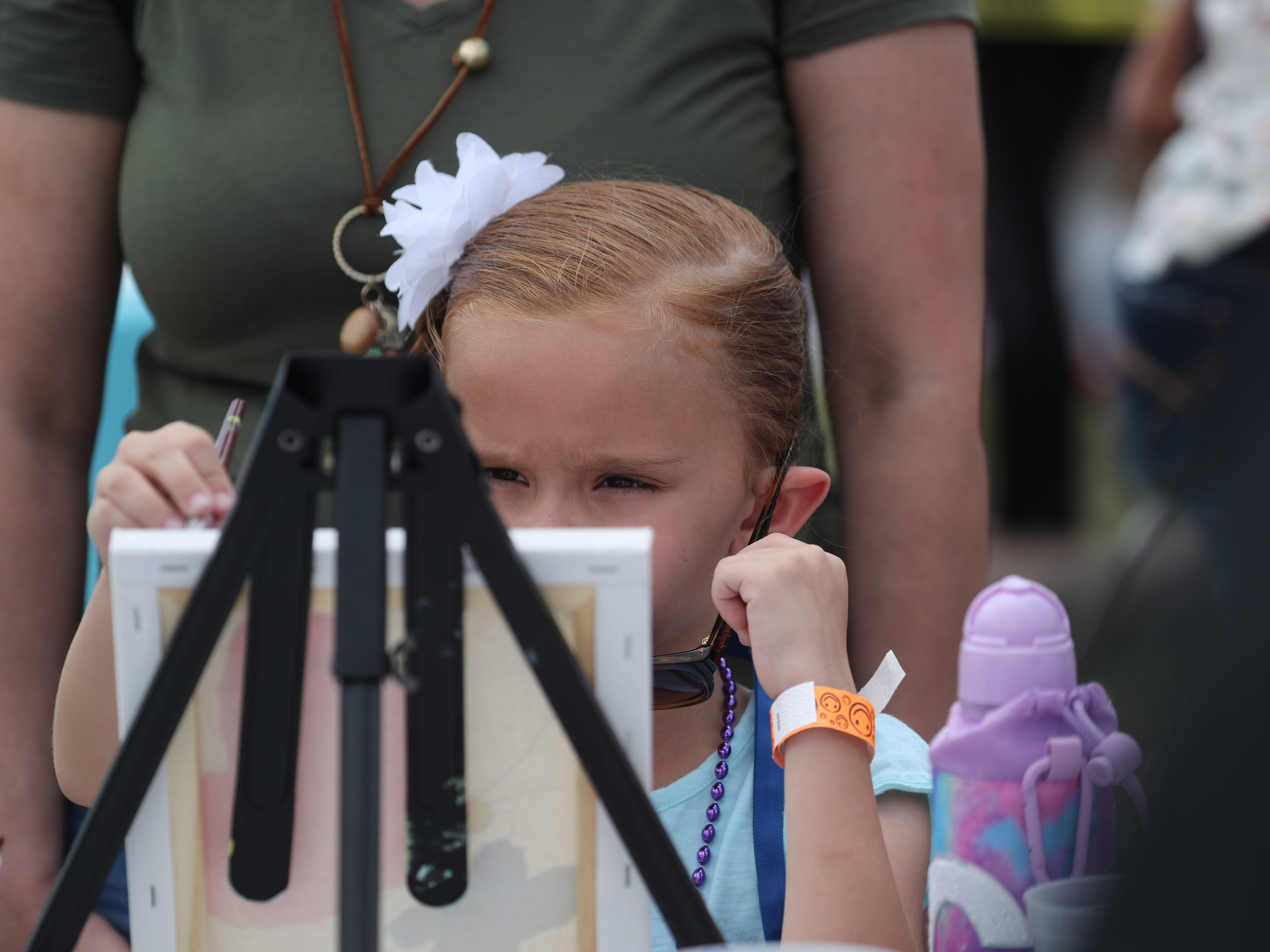 Carley Pilcher, 7, paints a butterfly at the Lights for Layla fundraiser on Saturday at Cape Assembly in Cape Coral.