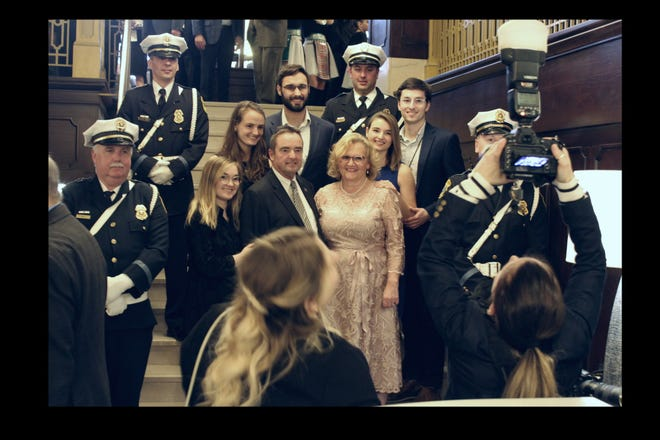 Green Bay Mayor Jim Schmitt and his family pose for a photo with police in dress uniforms during a celebration of the mayor's 16 years in office on Friday at the Hotel Northland.