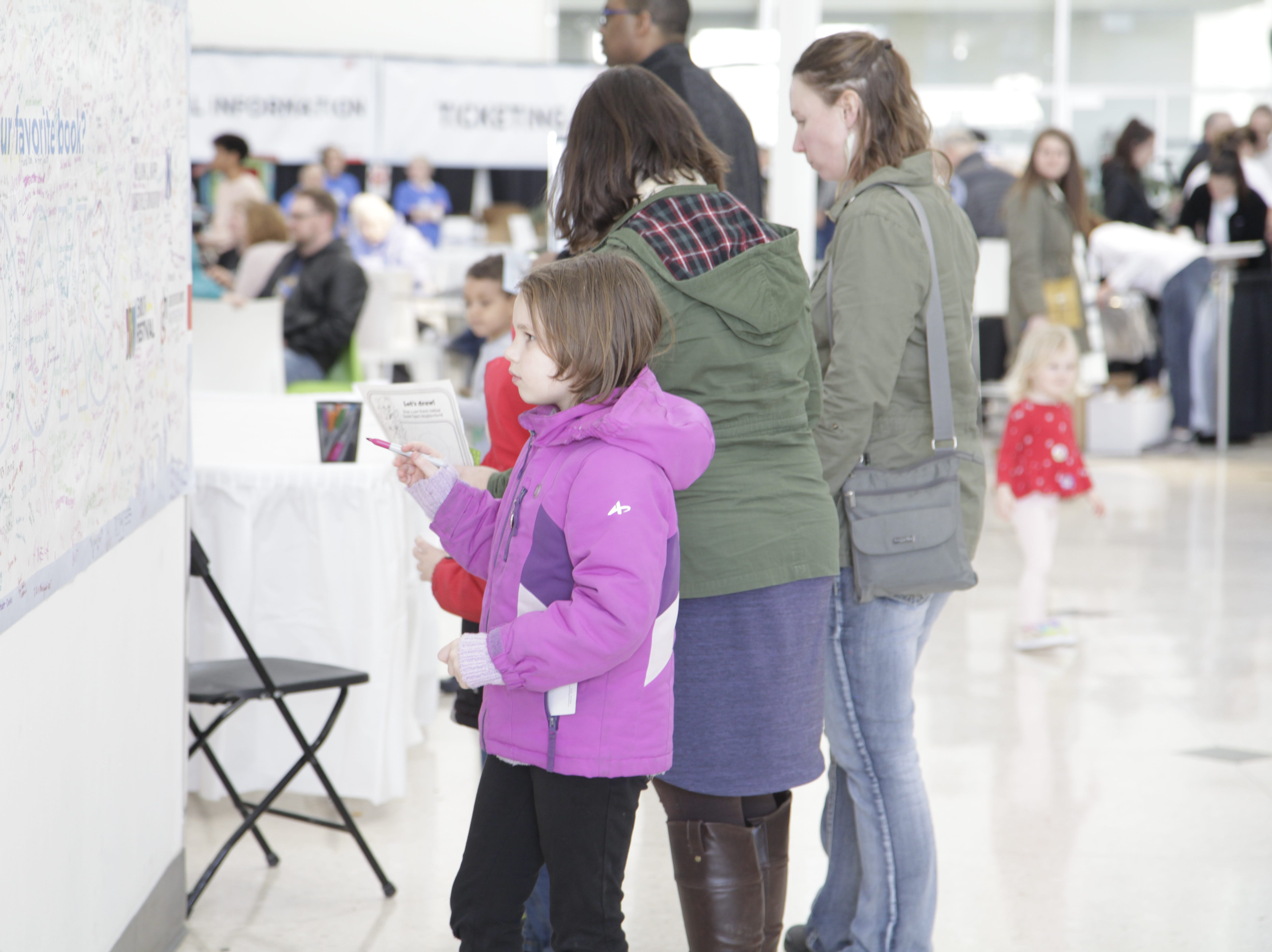 Ella Harden, 7, prepares to write her favorite book on a display at the DSM Book Festival, which attracted authors, speakers and book lovers to downtown Des Moines on Saturday, March 30, 2019.