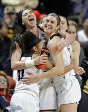 Iowa's Megan Gustafson, top left, embraces teammates Hannah Stewart and Tania Davis during the second half of a regional women's college basketball game against North Carolina State in the NCAA Tournament in Greensboro, N.C., Saturday, March 30, 2019. (AP Photo/Chuck Burton)