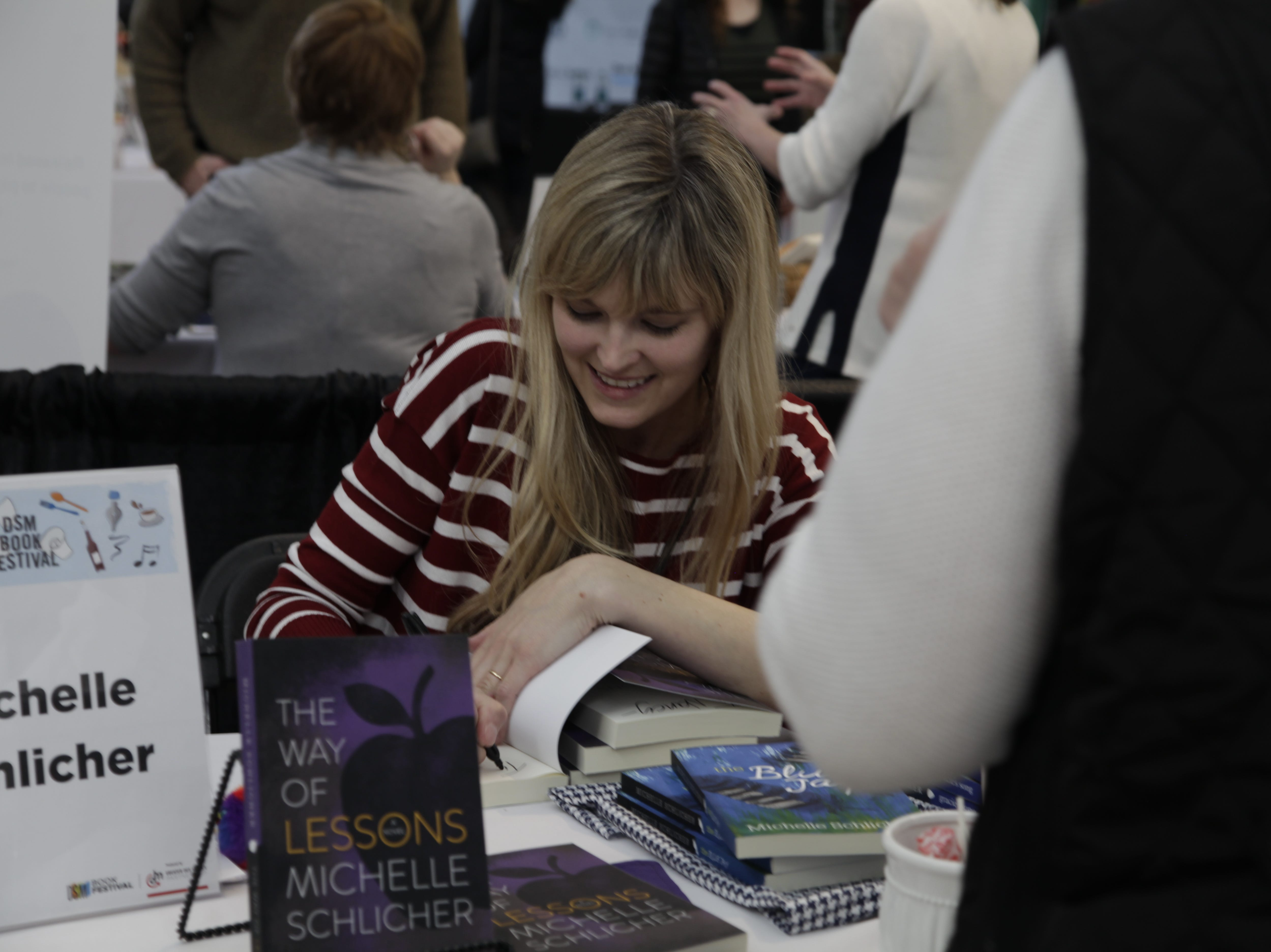 Ankeny author Michelle Schlicher signs a book at the DSM Book Festival downtown on Saturday, March 30, 2019.