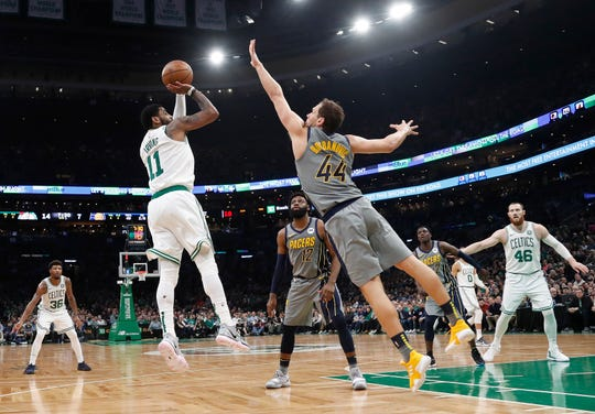 Boston Celtics' Kyrie Irving shoots over Indiana Pacers' Bojan Bogdanovic during the first quarter of an NBA basketball game Friday, March 29, 2019, in Boston. (AP Photo/Winslow Townson)