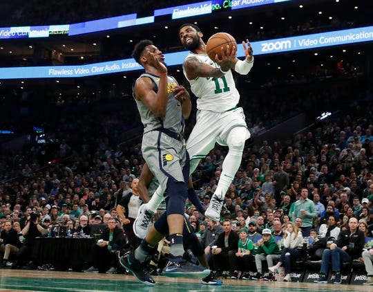 Boston Celtics' Kyrie Irving (11) looks to pass behind Indiana Pacers' Darren Collison during the second quarter of an NBA basketball game Friday, March 29, 2019, in Boston. (AP Photo/Winslow Townson)