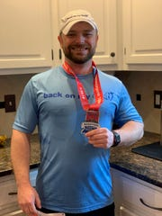 Matt Baker holds his medal after finishing the Carmel Marathon on Saturday, March 30, 2019. Baker was one of about 4,700 runners registered to participate in one of the four Carmel Marathon Weekend races.