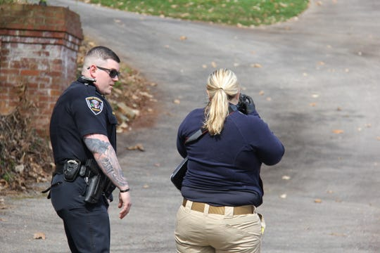 A law enforcement officer and medical examiner respond to the scene of a body found near the Tennessee River on Buckhead Trail in Knoxville on March 30, 2019
