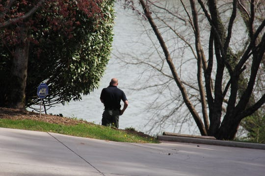 An officer responds to Buckhead Trail in Knoxville after a body was found near the Tennessee River on March 30, 2019.