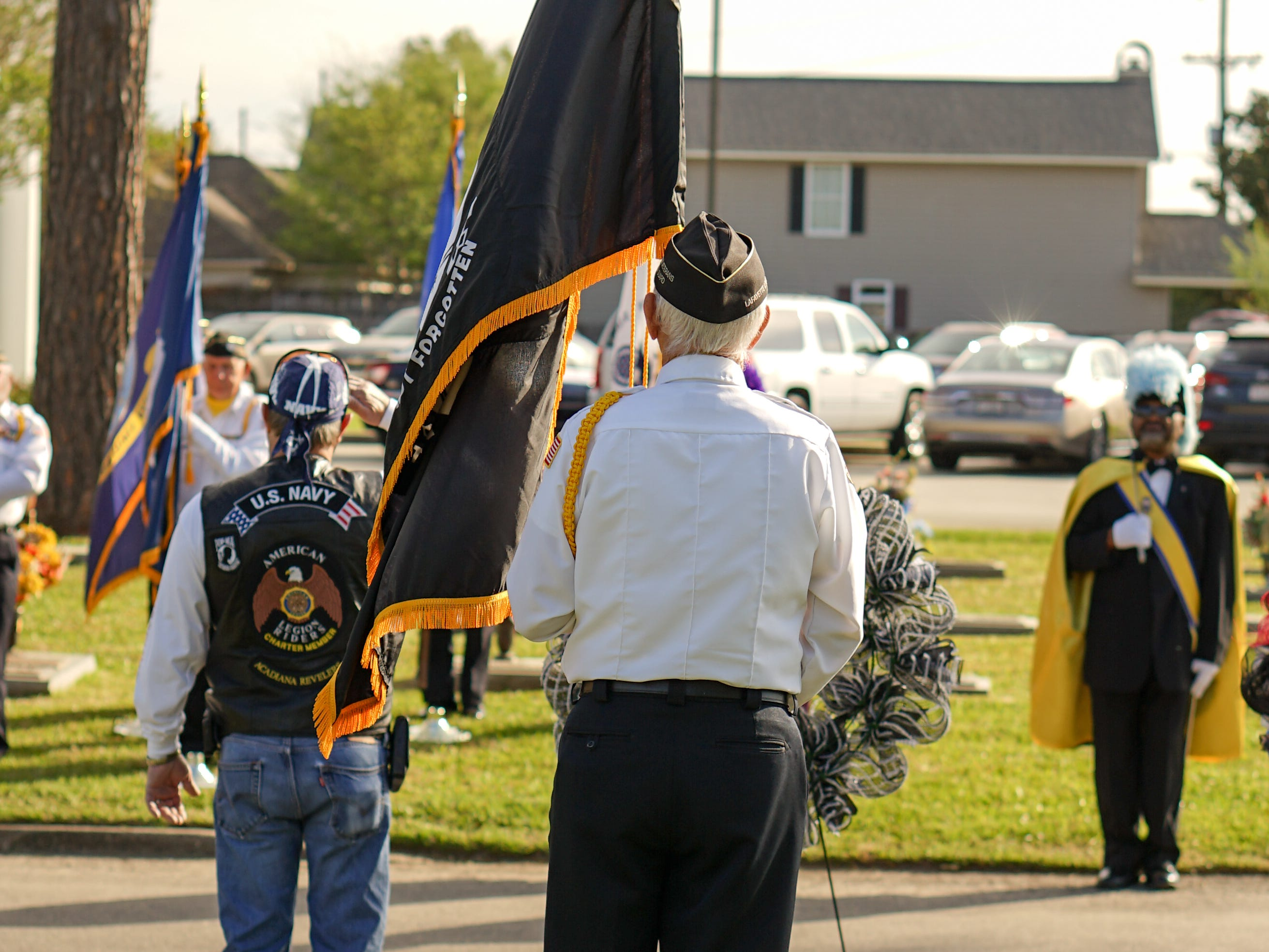 """Members of the Acadiana Veterans Honor Guard and onlookers stand before the memorial during the """"Welcome Home Vietnam Veterans"""" event at Fountain Memorial Funeral Home and Cemetery in Lafayette on Friday, March 29, 2019."""