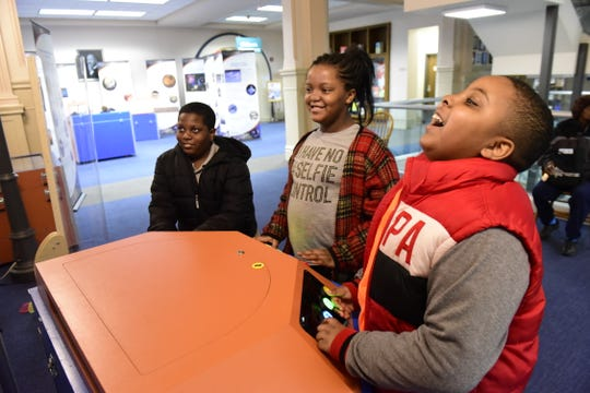 Educational games within the Discover NASA exhibit at the Mansfield/Richland County Public Library kept these three friends busy during Saturday's rainstorm. From left: Camryn Hood, 13; Kimaya Hood, 10; and Semaja Watts, 11. The extensive display gives children a complete experience of outer space, and will remain on the second floor of the library until May 30.