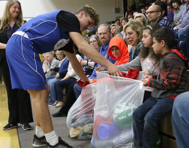 It's a tradition during pre-game introductions at the News Journal All-Star Basketball Classic for the players to give gifts from their schools to children representing the Rehab Center/Catalyst Life Services. Shelby's Uriah Schwemley is shown here adding to the gifts collected by siblings Jayden, Brooklynn and Dustin Moore of Lexington. Complete coverage of the 41st Classic can be found in today's Sports section.