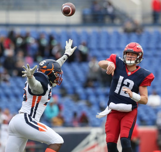 Memphis Express quarterback Brandon Silvers throws the ball over the outstretched hand of Orlando Apollos defender Andrew Ankrah during their game at the Liberty Bowl Memorial Stadium on Saturday, March 30, 2019.
