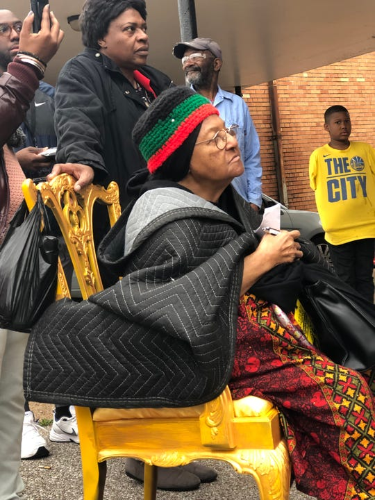 "Regina ""Mother"" King, seated in a gold chair to signify her status as a community elder, listens as Carnita Atwater addresses North Memphis community members gathered in front of New Chicago's community center."