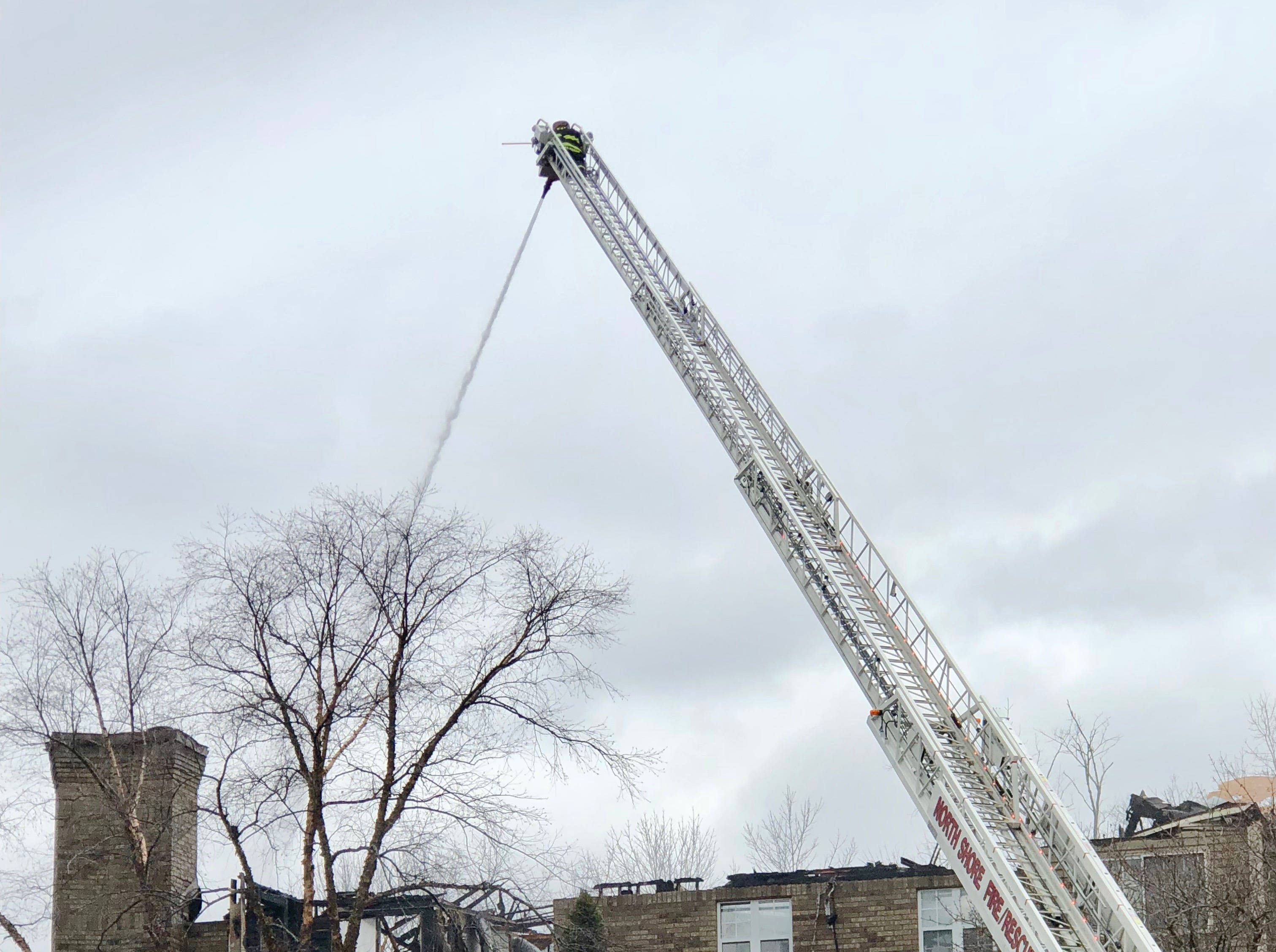 A ladder truck continues to spray hot spots at a White Oaks apartment building in Bayside where a fire destroyed a unit.