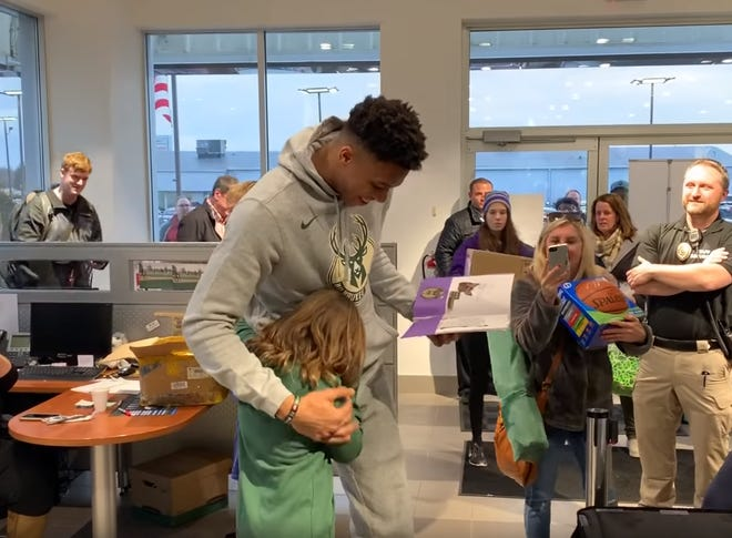 Giannis Antetokounmpo hugs 11-year-old Lily after she gave him a folder full of artwork she made for him. A video of the hugs went viral on social media Friday.