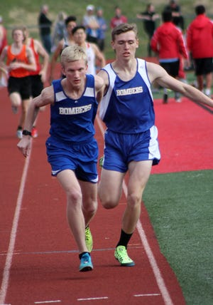 Mountain Home's Bob Allen hands to Whit Lawrence during a relay on Thursday evening at Branson, Mo.