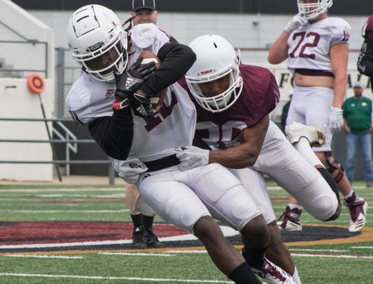 Logan Latin (29) attempts to tackle Markis McCray (12) during University of Louisiana at Monroe's Spring scrimmage at Malone Stadium in Monroe, La. on March 30.