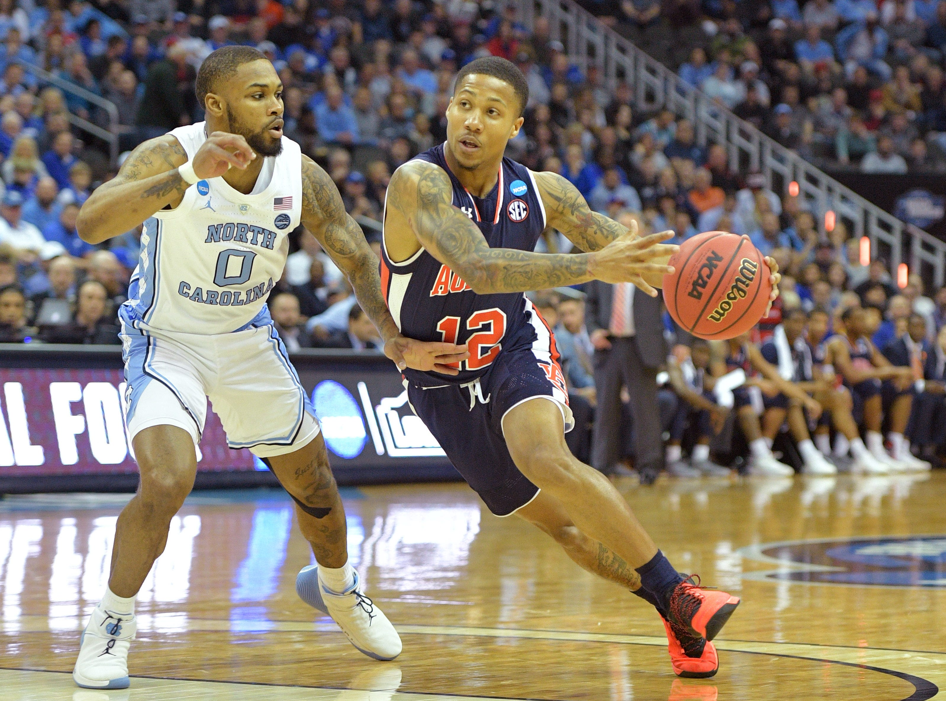 Auburn Tigers guard J'Von McCormick (12) drives to the basket against North Carolina Tar Heels guard Seventh Woods (0) during the first half in the semifinals of the midwest regional of the 2019 NCAA Tournament at Sprint Center.