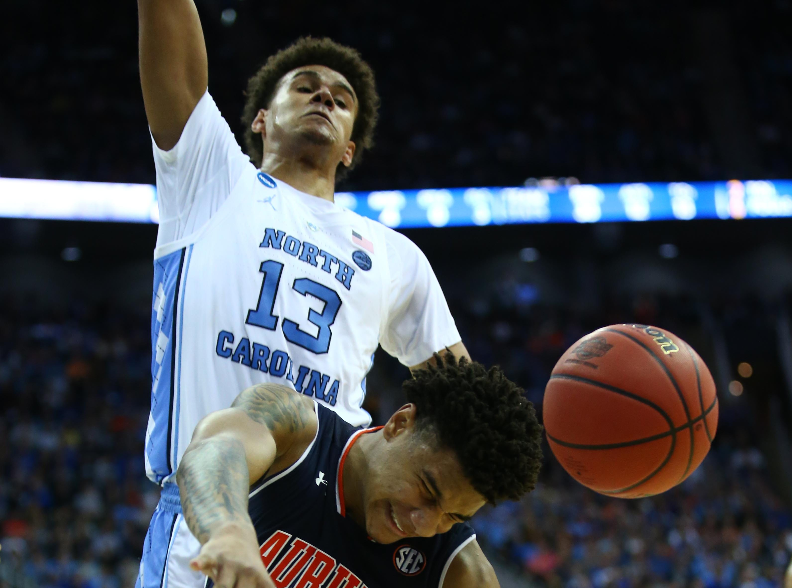 Mar 29, 2019; Kansas City, MO, United States; Auburn Tigers forward Chuma Okeke (5) suffers an apparent injury as he drives to the basket against North Carolina Tar Heels guard Cameron Johnson (13) during the second half in the semifinals of the midwest regional of the 2019 NCAA Tournament at Sprint Center. Mandatory Credit: Jay Biggerstaff-USA TODAY Sports
