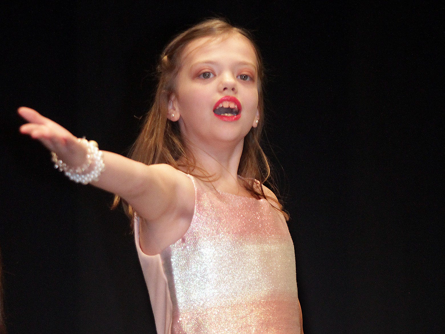 Avery Nixon (9) blows a kiss to the audience at The Sparkle Pageant at Pope John Paul II High School on Saturday, March 30, 2019.