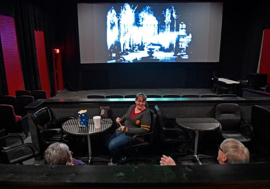 April Klein talks with friends as a 1930s zombie movie plays before the main feature at the Full Moon Cineplex. Klein is a regular at the Hermitage theater, which shows horror films with some other classics mixed in.