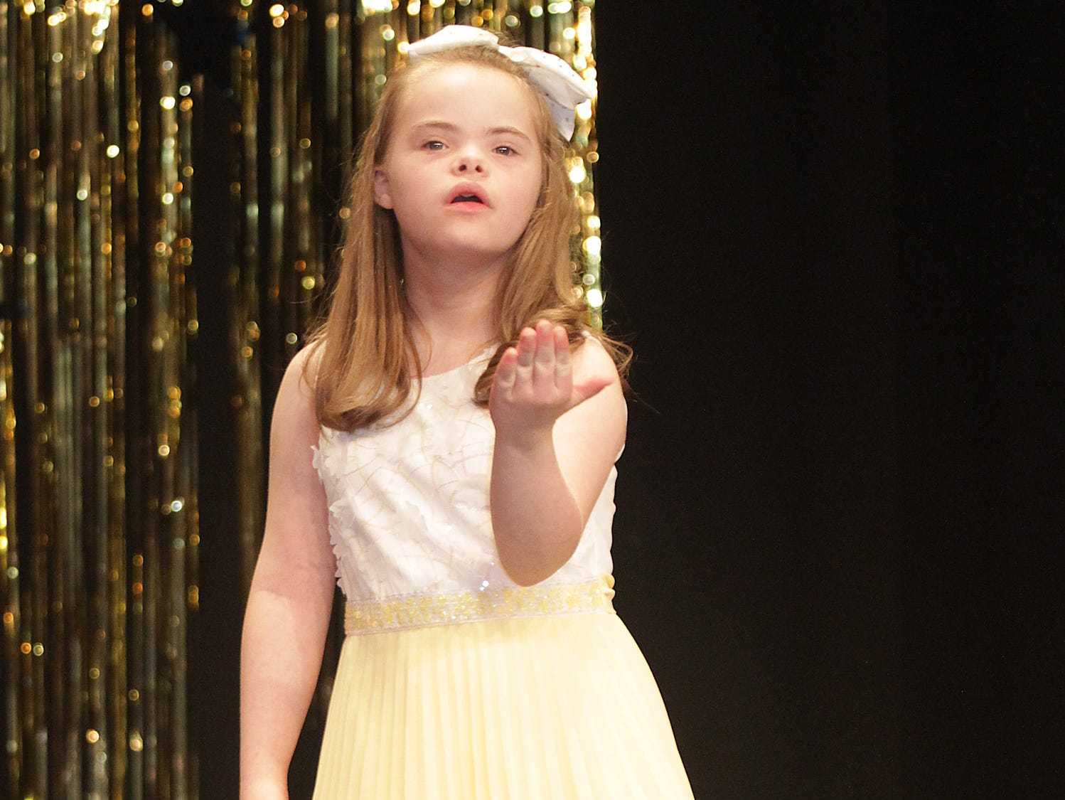 Lillian Satterfield (11) blows a kiss to the audience at The Sparkle Pageant at Pope John Paul II High School on Saturday, March 30, 2019.