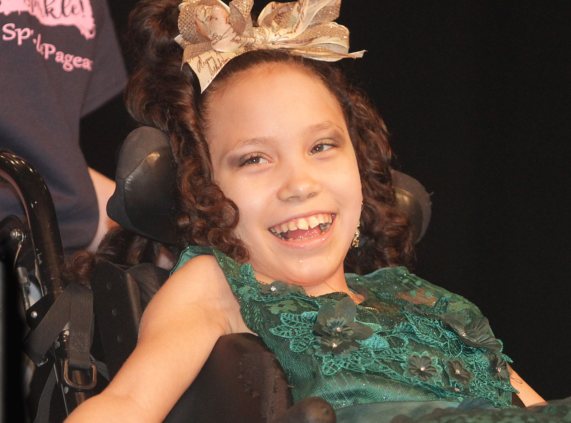 Kylee Abrams (12) smiles big as she enjoys being in The Sparkle Pageant at Pope John Paul II High School on Saturday, March 30, 2019.