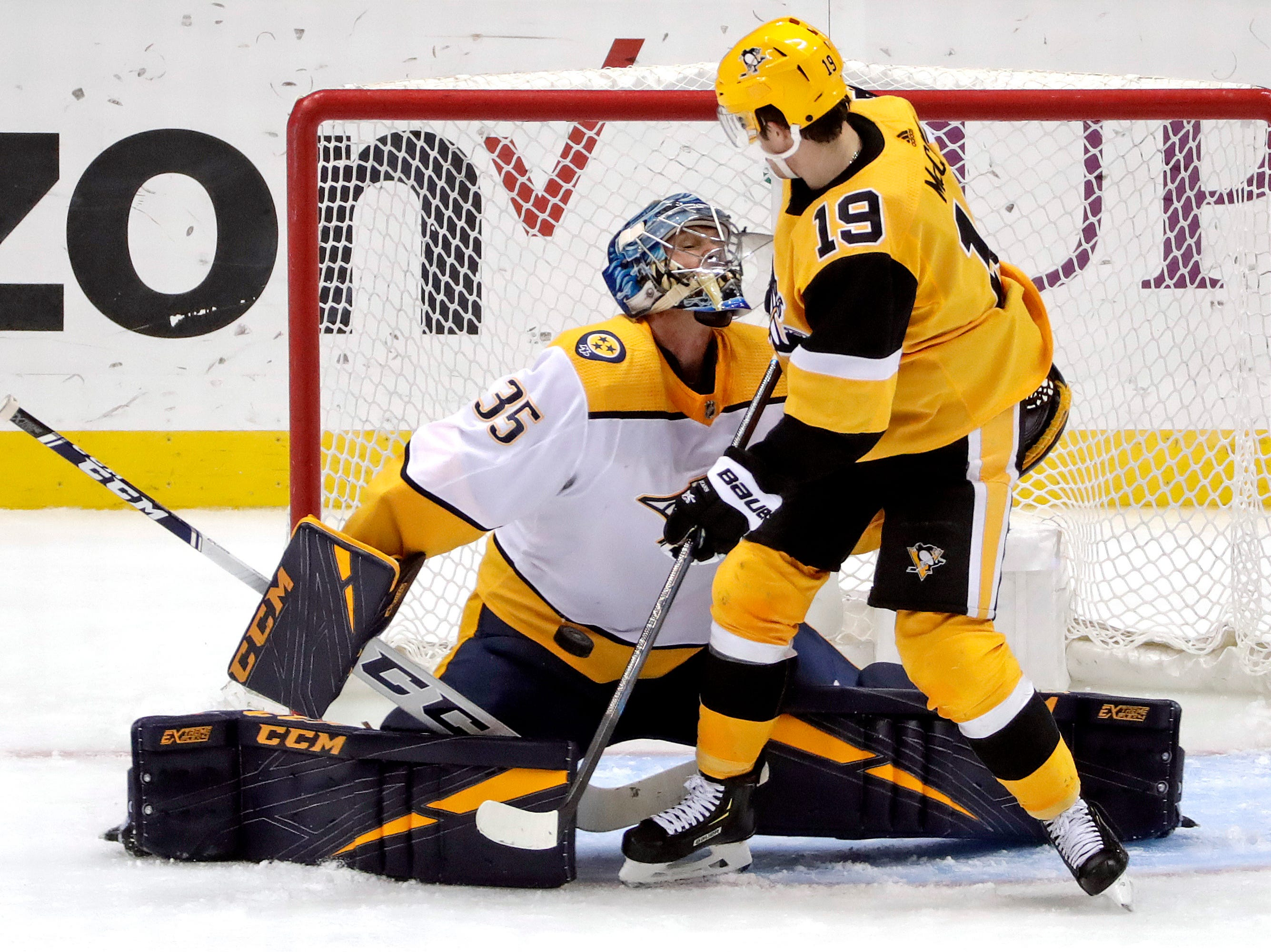Nashville Predators goaltender Pekka Rinne (35) stops a shot with Pittsburgh Penguins' Jared McCann (19) screening him and looking for a rebound during the third period of an NHL hockey game in Pittsburgh, Friday, March 29, 2019. (AP Photo/Gene J. Puskar)