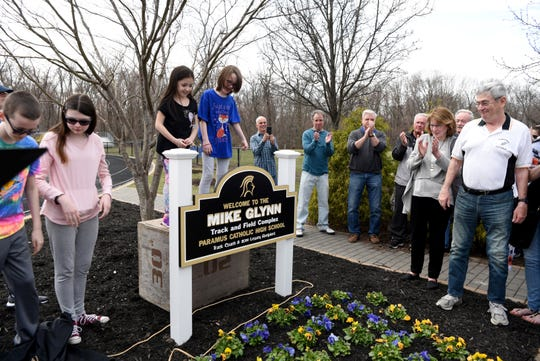 "The Paramus Catholic track has been named ""Mike Glynn Track and Field Complex,"" after former Hall of Fame coach Mike Glynn, on right. Glynn smiles after his grandchildren unveil the new sign on Saturday, March 30, 2019."