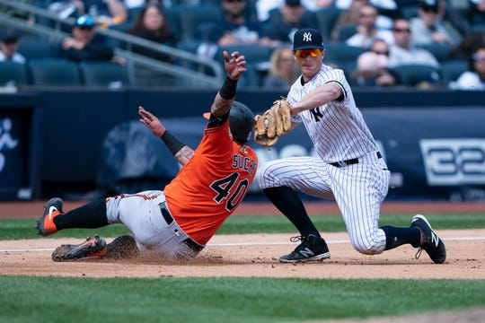 Baltimore Orioles catcher Jesus Sucre (40) avoids a tag by New York Yankees third baseman DJ LeMahieu (26) to advance to third base on a fly ball during the sixth inning at Yankee Stadium.