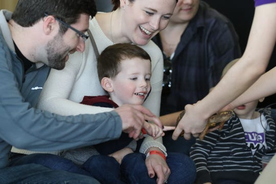 Jack Schneider 2 of Clark touches a turtle as part of the third annual Rare Disease Day held at the Liberty Science Center in Jersey City on March 30, 2019. He is with his parents John and Jessica.