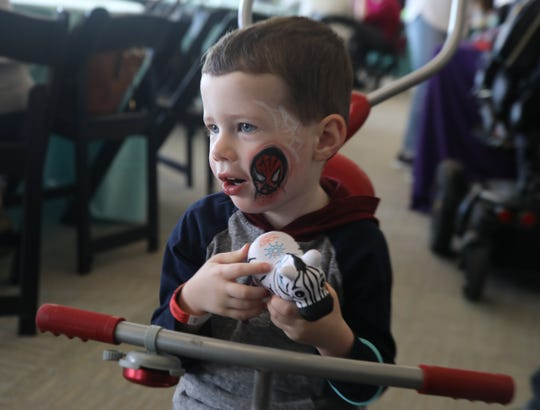 This is Jack Schneider 2 of Clark holds a toy zebra that was given to him at the third annual Rare Disease Day held at the Liberty Science Center in Jersey City on March 30, 2019. Jack has congenital muscular dystrophy but rode his tricycle around the room.