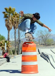 Jon Rogers jumps a traffic barrel with his skateboard at the Las Cruces skatepark on March 28, 2019.