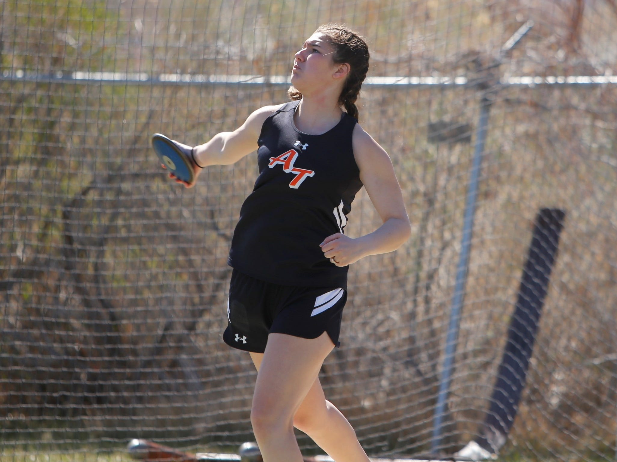 Aztec's Sadie Garcia pivots to throw her discus downfield in the girls discus during Saturday's FHS Invitational at Hutchison Stadium.