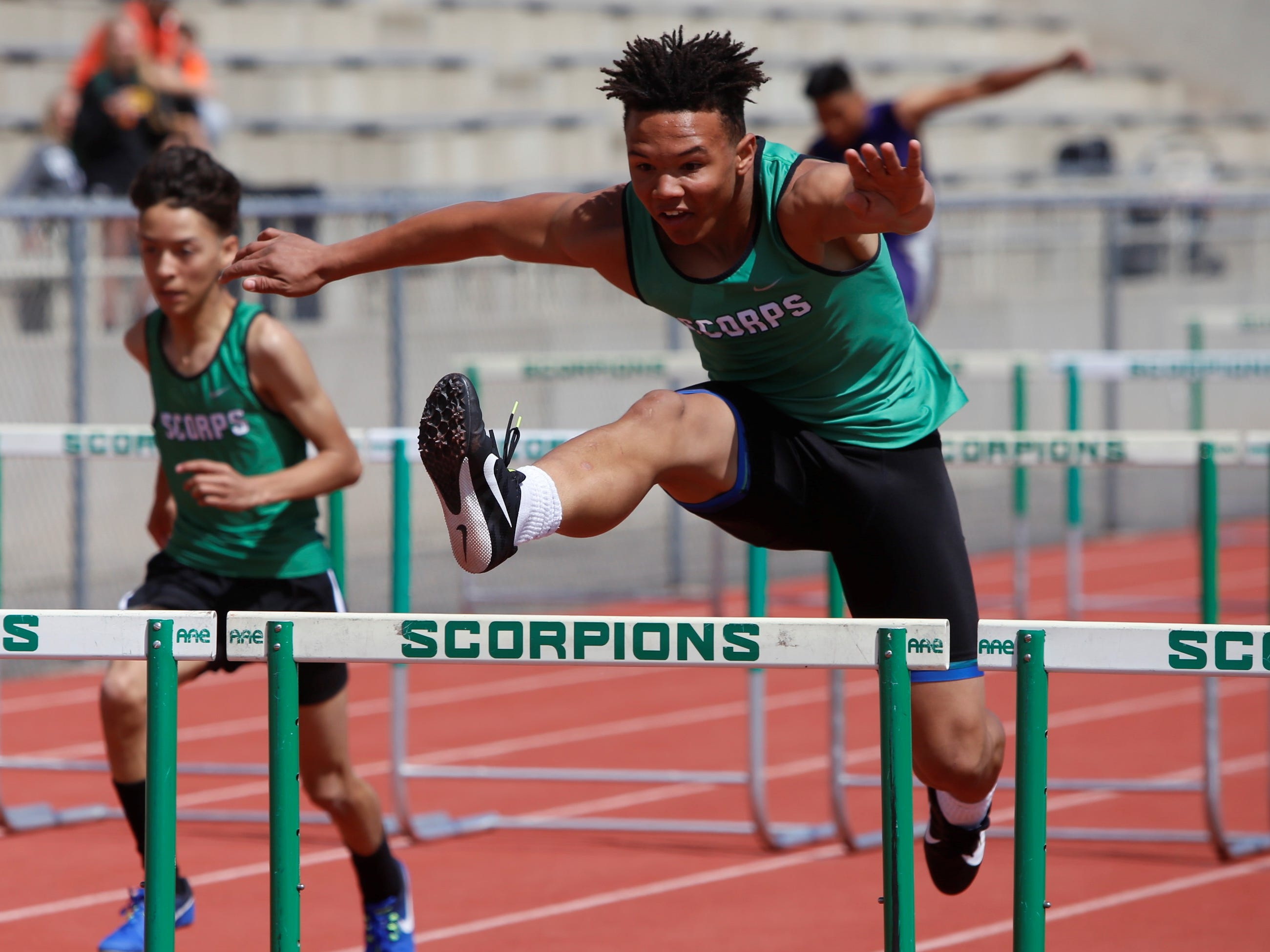 Farmington's Jackie Dunning jumps over the hurdle in the first heat of the boys 110-meter hurdles during Saturday's FHS Invitational at Hutchison Stadium.