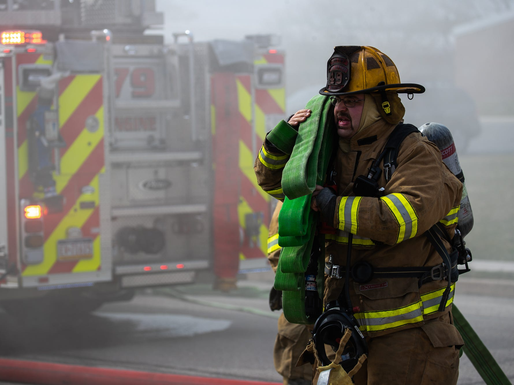 Firefighter Jerry Misner pulls a second hoseline at the scene of a house fire on the 100 block of Mumma Ave., Saturday, March 30, 2019, in Penn Township. No one was injured in the fire, which appears to have been an accidental fire in the kitchen, said Hanover Area Fire & Rescue Chief Tony Clousher.