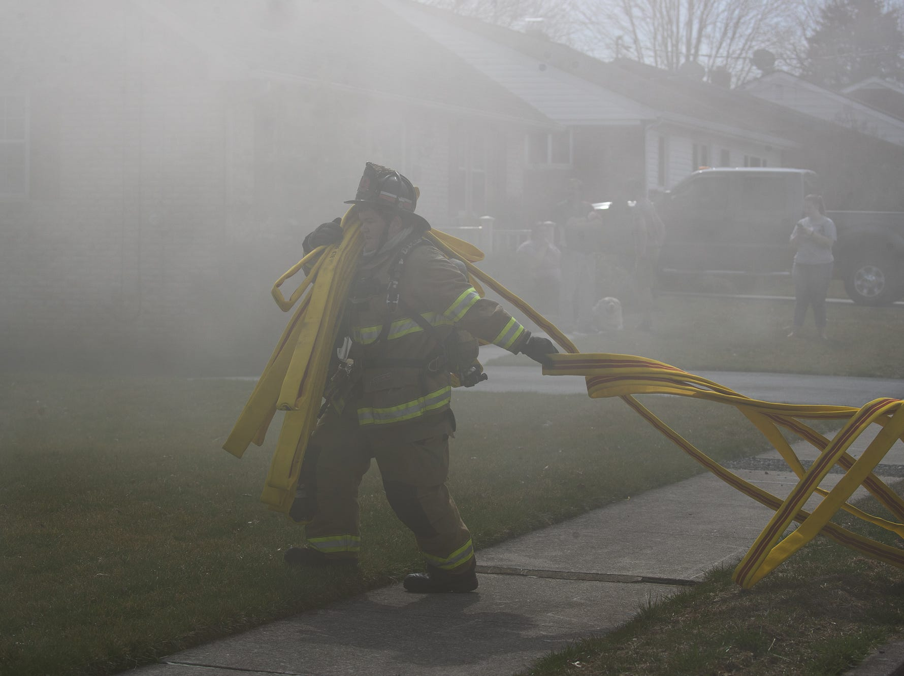 Volunteer firefighter Brady Cromer pulls a two-inch hoseline to begin the initial interior attack at the scene of a house fire on the 100 block of Mumma Ave., Saturday, March 30, 2019, in Penn Township. No one was injured in the fire, which appears to have been an accidental fire in the kitchen, said Hanover Area Fire & Rescue Chief Tony Clousher.