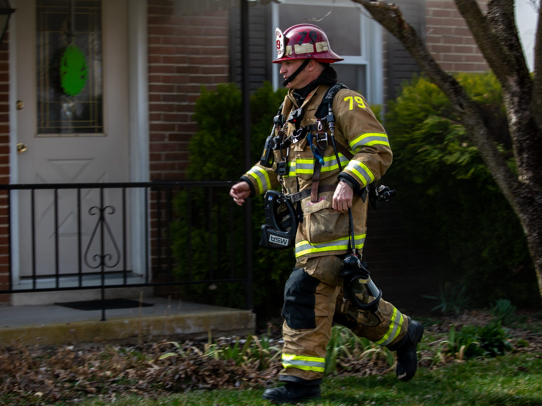 Captain Geoff Miller heads to the front door to begin the initial interior fire attack at the scene of a house fire on the 100 block of Mumma Ave., Saturday, March 30, 2019, in Penn Township. No one was injured in the fire, which appears to have been an accidental fire in the kitchen, said Hanover Area Fire & Rescue Chief Tony Clousher.