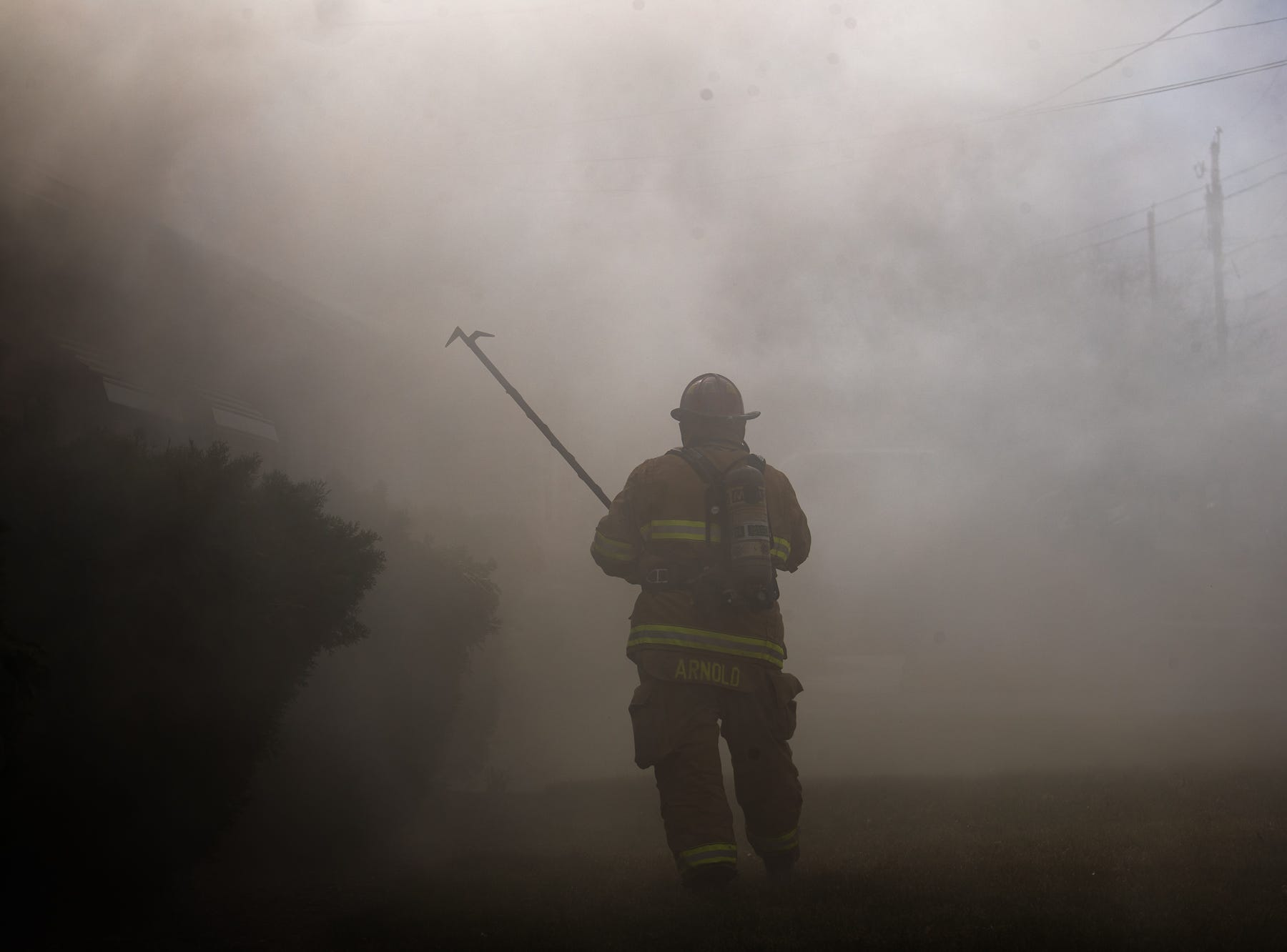 Firefighter Chad Arnold works at the scene of a house fire on the 100 block of Mumma Ave., Saturday, March 30, 2019, in Penn Township. No one was injured in the fire, which appears to have been an accidental fire in the kitchen, said Hanover Area Fire & Rescue Chief Tony Clousher.
