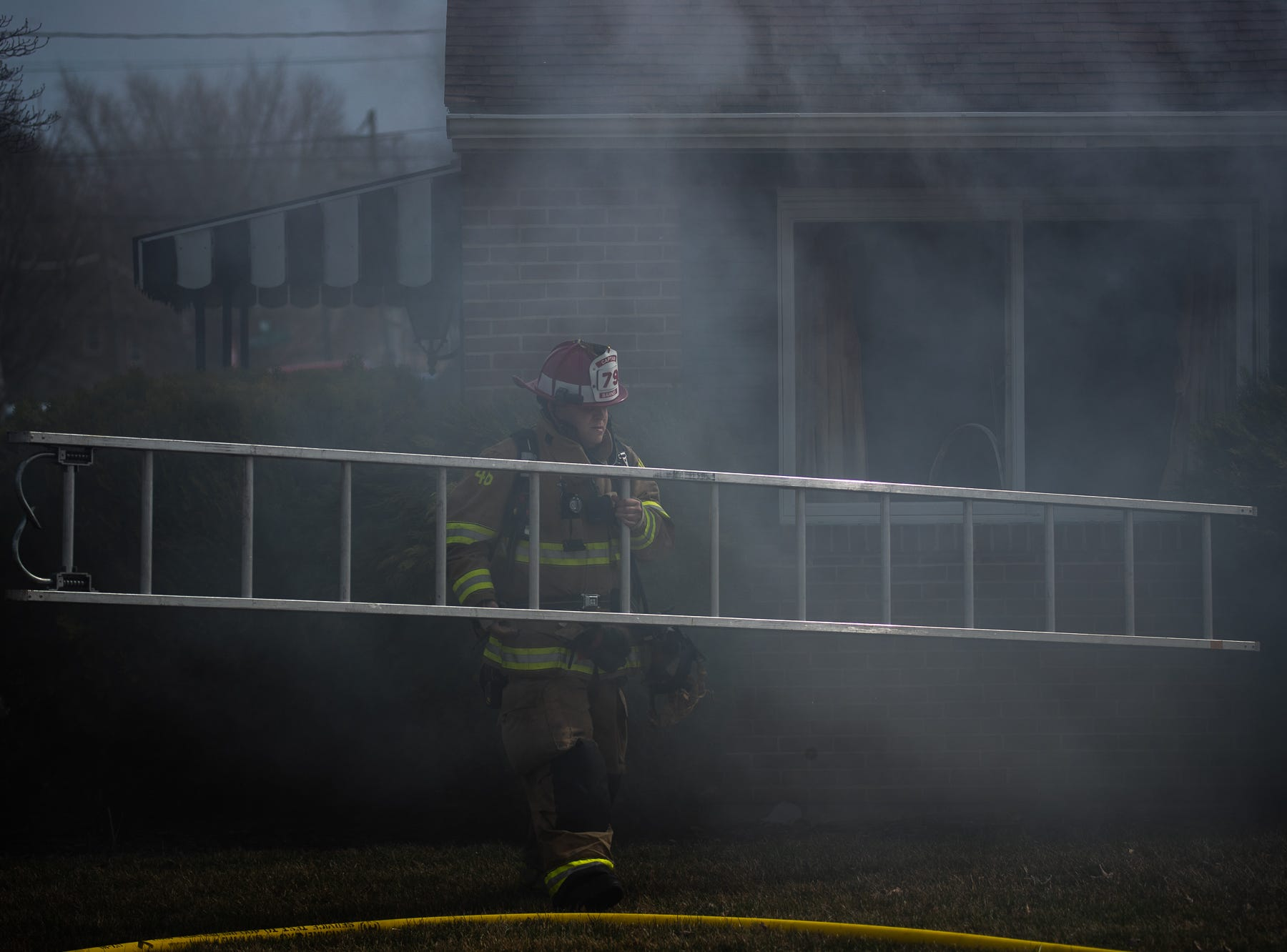 Firefighter Matt Barnes carries a ground ladder at the scene of a house fire on the 100 block of Mumma Ave., Saturday, March 30, 2019, in Penn Township. No one was injured in the fire, which appears to have been an accidental fire in the kitchen, said Hanover Area Fire & Rescue Chief Tony Clousher.