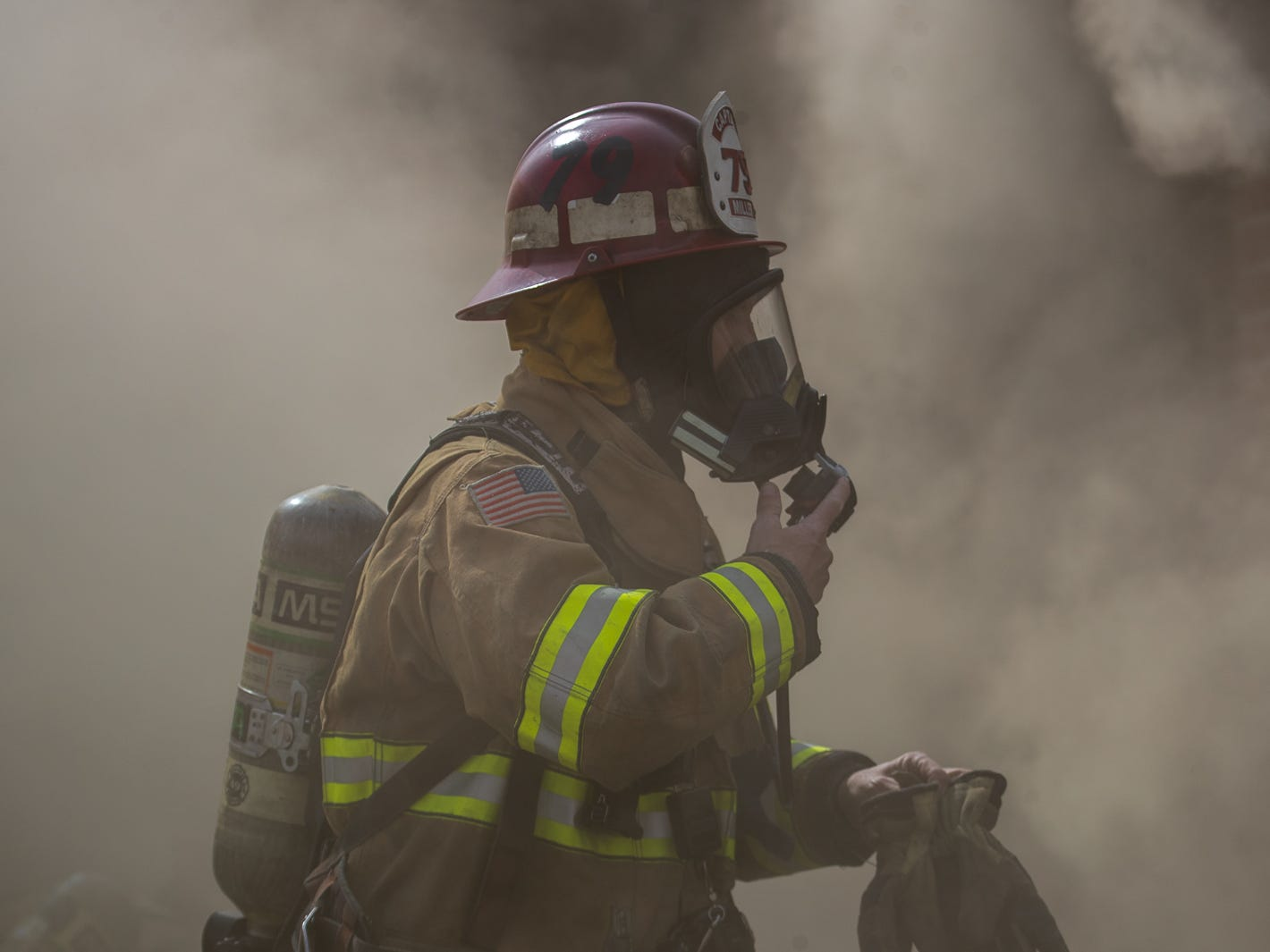 Captain Geoff Miller gears up to begin the initial interior attack at the scene of a house fire on the 100 block of Mumma Ave., Saturday, March 30, 2019, in Penn Township. No one was injured in the fire, which appears to have been an accidental fire in the kitchen, said Hanover Area Fire & Rescue Chief Tony Clousher.