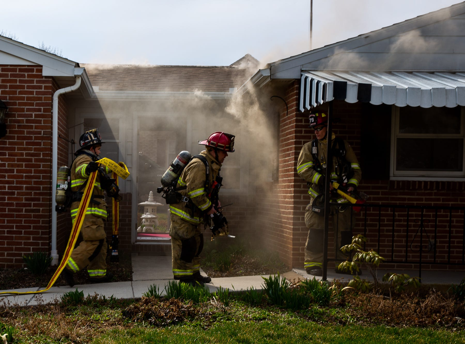 Firefighters gear up to begin the initial interior attack at the scene of a house fire on the 100 block of Mumma Ave., Saturday, March 30, 2019, in Penn Township. No one was injured in the fire, which appears to have been an accidental fire in the kitchen, said Hanover Area Fire & Rescue Chief Tony Clousher.