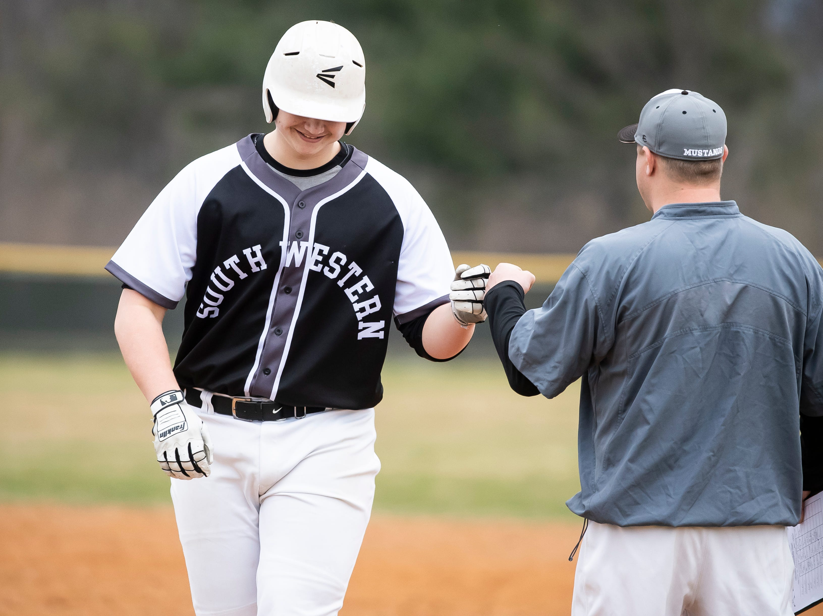 South Western's Zack Reed fist bumps assistant coach Nate Brodbeck after getting on base during a game against Carlisle in Hanover on Friday, March 29, 2019. The Mustangs won 11-9.