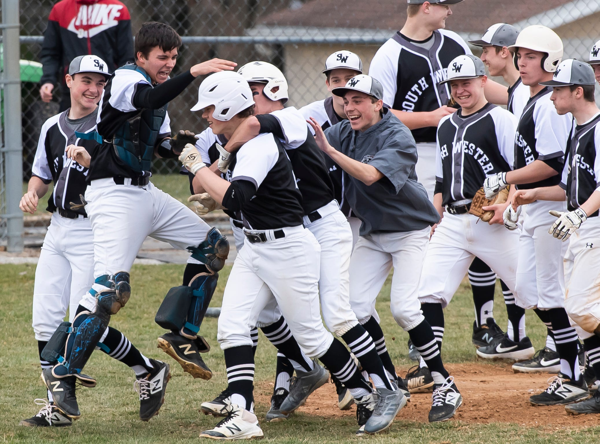 South Western's Ty Cromer (4) is mobbed by his teammates at home plate after hitting a 3-run homer against Carlisle in Hanover on Friday, March 29, 2019. The Mustangs won 11-9.